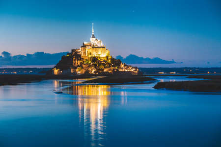 Classic view of famous Le Mont Saint-Michel tidal island in beautiful twilight during blue hour at dusk, Normandy, northern France 新聞圖片