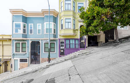 Classic urban scene of historic colorful buildings along one of San Francisco's steepest streets near Telegraph Hill residential area district on a beautiful sunny day in summer, SF, California, USA 新聞圖片