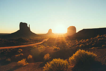 Classic view of scenic Monument Valley with the famous Mittens and Merrick Butte in beautiful golden morning light at sunrise in summer with retro vintage