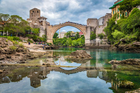 Classic view of the famous Old Bridge of Mostar (Stari Most), on a rainy day with dark clouds in summer, Bosnia and Herzegovina