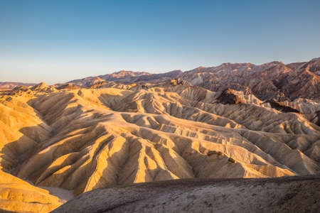 Scenic panoramic view of amazing sandstone formations at famous Zabriskie Point viewpoint in beautiful golden evening light at sunset, Death Valley National Park, California, USA