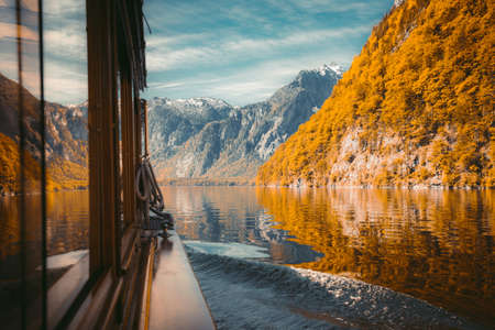 Traditional passenger boat gliding on Lake Konigssee with Watzmann mountain in the background on a beautiful sunny day in fall, Berchtesgadener Land, Bavaria, Germany 版權商用圖片