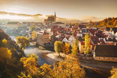 Panoramic view of the historic city of Cesky Krumlov with famous Cesky Krumlov Castle, a UNESCO World Heritage Site since 1992, in beautiful golden morning light at sunrise with fog in fall, Czech Republic