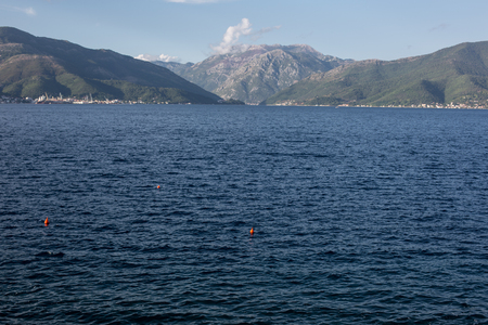 Wavie sea with mountains and light blue sky in the background