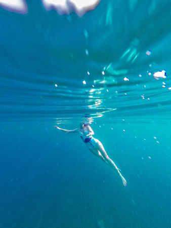 Underwater shot of girl swimming in a  sea, with sunbeam comming trough water