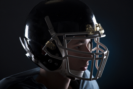 Close up of a football player with a blue uniform on a black background