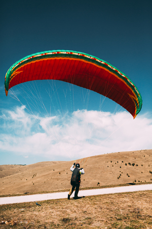 Man landing with paraglider Imagens - 105099162