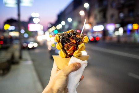 Male hand holding a dessert crepes with a defocused urban background