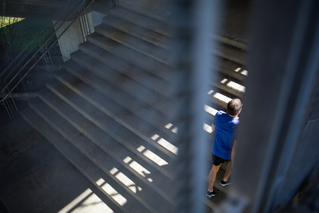Male runner climbing up the stairs with ease, viewed troug wire fence