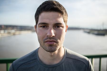 Serious male runner posing on a bridge Imagens