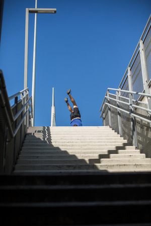 Male athlete doing a handstand on a bridge, urban scenery
