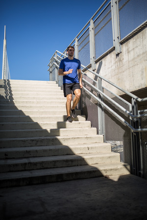 Male athlete exercising, running down the stairway