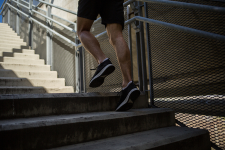 Close up shot of runners legs and shoes while running up steps Imagens