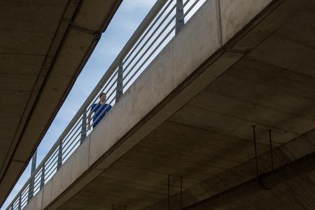 Male athlete running on a bridge, urban scenety,  viewed from below