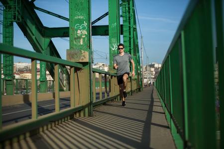 Handsome male runner jogging on a bridge, urban scenery Imagens