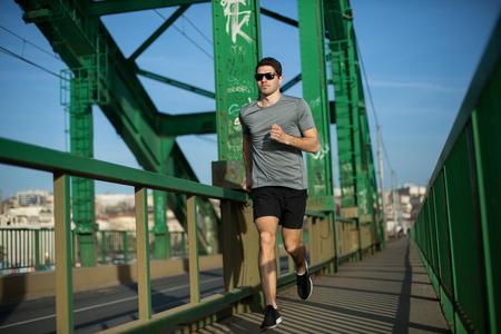 Handsome male runner jogging on a bridge, urban scenery 免版税图像