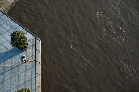 Overhead view of male athlete stretching his leg on a railing, beside a river