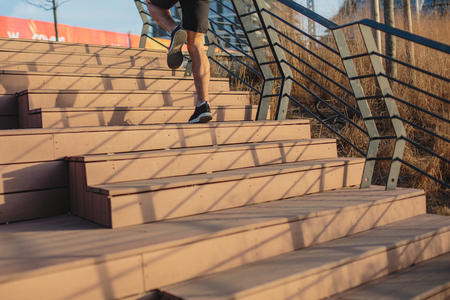 Male athlete climbing up the stairs beside a river, urban scenery
