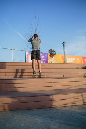 Male athlete doing box jumps in an urban scenery, beside a river Imagens - 104975287