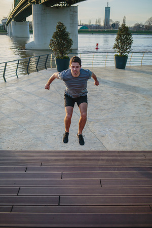 Male athlete doing box jumps in an urban scenery, beside a river