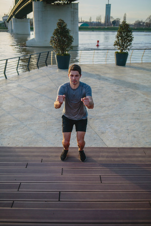Male athlete doing box jumps in an urban scenery, beside a river Imagens - 104975290