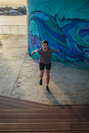 Male athlete doing box jumps in an urban scenery, beside a river Imagens - 104975294