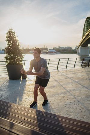 Male athlete doing box jumps in an urban scenery, beside a river Imagens - 104975297