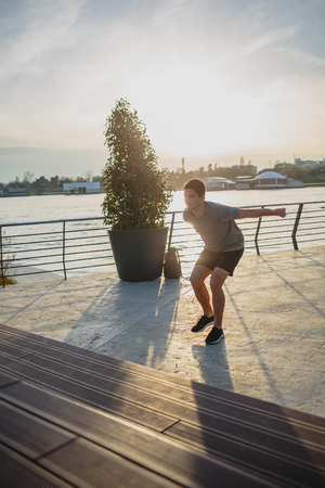 Male athlete doing box jumps in an urban scenery, beside a river Imagens - 104975296