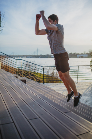 Male athlete doing box jumps in an urban scenery, beside a river Imagens - 104975298