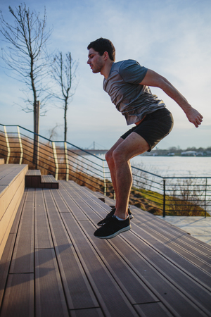 Male athlete doing box jumps in an urban scenery, beside a river Imagens - 104975300
