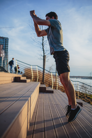 Male athlete doing box jumps in an urban scenery, beside a river Imagens - 104975301