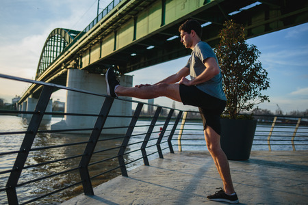 Male athlete stretching his leg on a railing Imagens - 104975302
