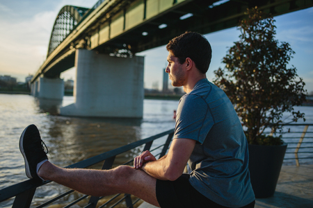 Male athlete stretching his leg on a railing Imagens - 104975303
