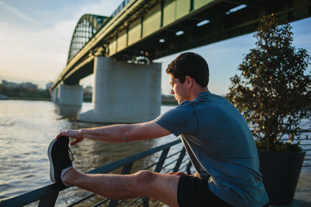 Male athlete stretching his leg on a railing Imagens - 104975308
