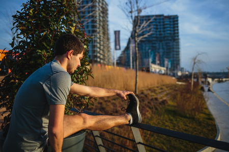 Male athlete stretching his leg on a railing Imagens - 104975307