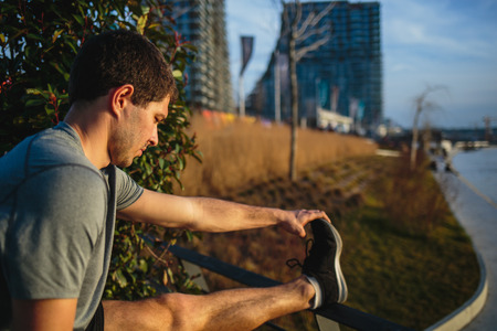 Male athlete stretching his leg on a railing Imagens - 104975305