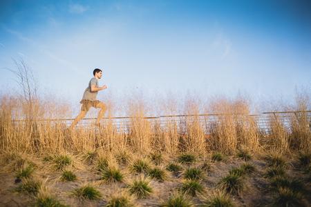 Male runner jogging on a riverside Imagens - 104975313