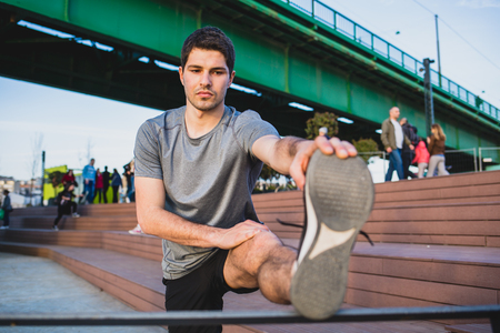 Male athlete stretching his leg on a railing Imagens - 104975318