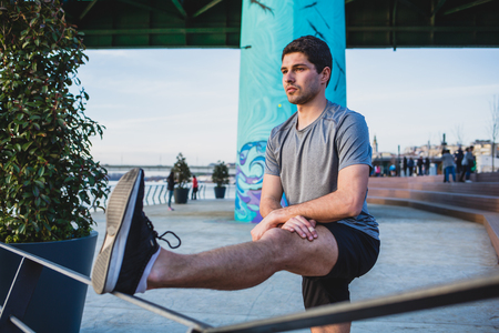 Male athlete stretching his leg on a railing Imagens - 104975330