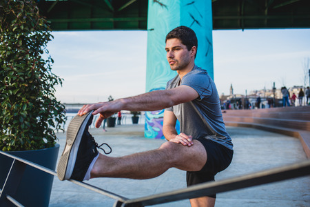 Male athlete stretching his leg on a railing