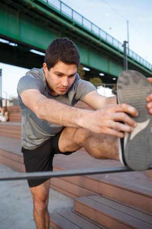 Male athlete stretching his leg on a railing Imagens - 104975322