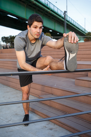 Male athlete stretching his leg on a railing Imagens - 104975324