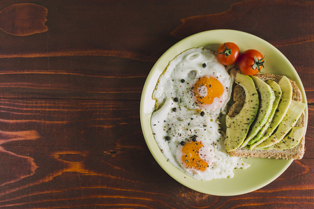 Plate of fried eggs, cherry-tomatoes and avocado on a toast Imagens - 105107888
