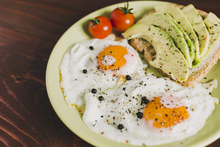 Plate of fried eggs, cherry-tomatoes and avocado on a toast Imagens - 105107896