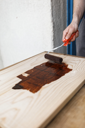 Man painting (dye) wooden plank with a roller Imagens - 104975327
