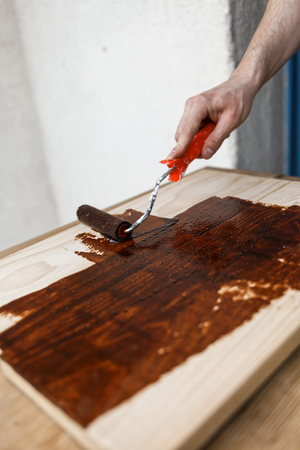 Man painting (dye) wooden plank with a roller Imagens - 104975329