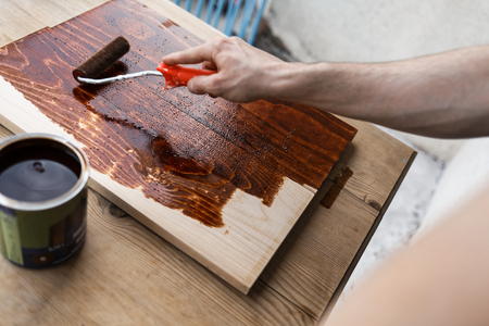 Man painting (dye) wooden plank with a roller