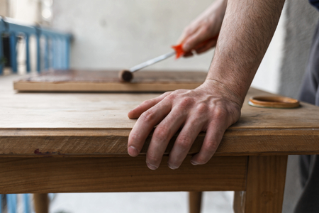 Man painting (dye) wooden plank with a roller Imagens - 104975332