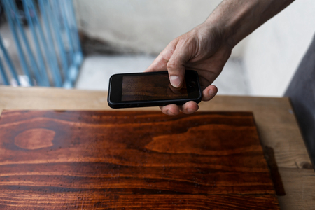 Male hand holding a cell phone and taking a image of a freshly painted wooden plank Imagens - 104975350