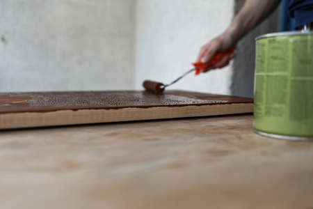 Man painting (dye) wooden plank with a roller Imagens - 104975353